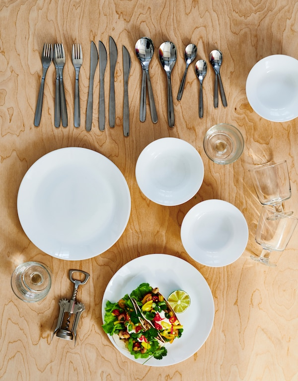 Tableware on a light wooden surface: white OFTAST plates and bowls, MOPSIG cutlery, wine glasses and a wine-bottle opener.