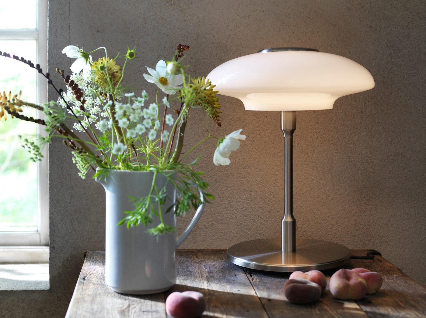 TÄLLBYN table lamp designed with Art Deco inspiration placed on a wooden table with a jug of flowers and peaches.