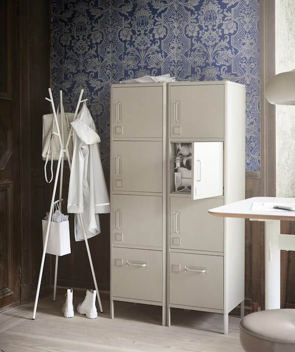 Tall metal cabinets next to a coat stand in the corner of an office space with blue patterned wallpaper.
