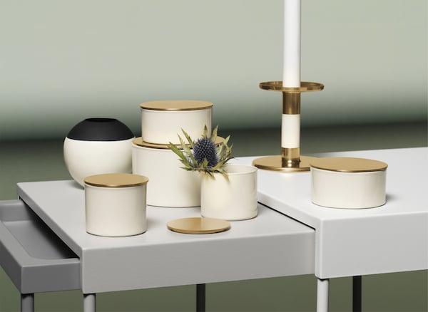 套桌上展示着象牙白、黑色和金色的储物盒、花瓶和烛台。