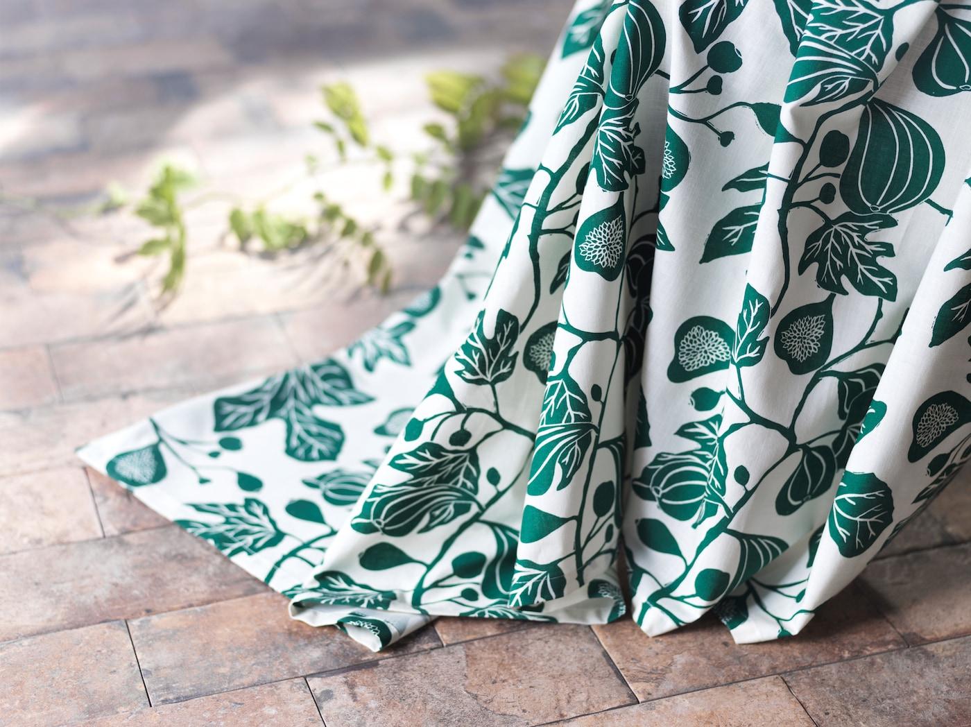 特写:白色和绿色的 ALPKLÖVER 奥普略福 拖地窗帘上饰有卷绕在一起的无花果叶子图案。