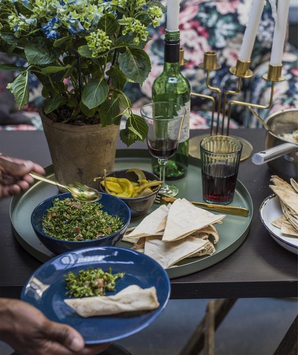 特写:餐桌上摆放着绿色托盘及碗,里面盛装着食物,还有一双手正将食物分至盘中。