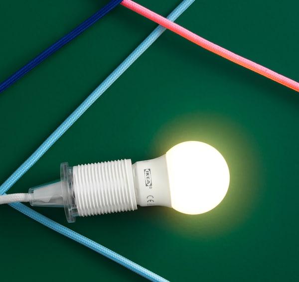 特写:绿色背景上有一个已点亮的LED灯泡。