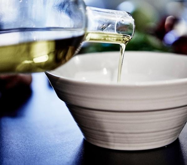特写:木质餐桌上的白碗中装着土豆丁和蔬菜。