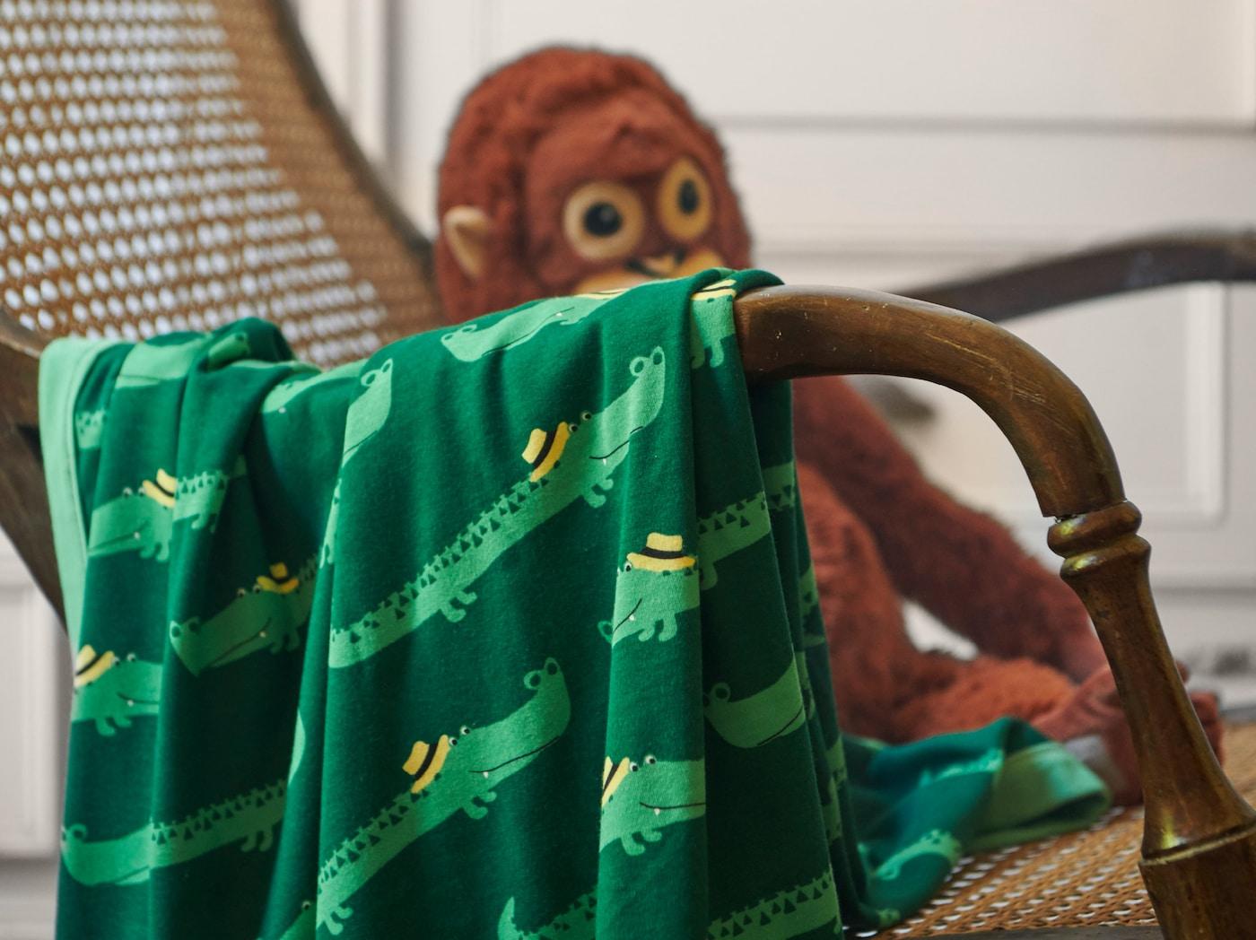 特写:RÖRANDE 略朗德 毯子置于柳条椅上,饰有在绿色背景上爬行的友好小鳄鱼。