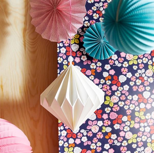 特写:悬挂着的白色、粉色和青绿色纸质装饰。
