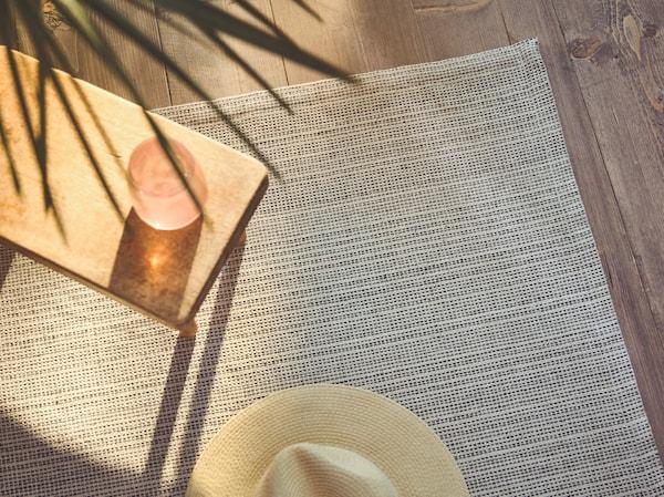 特写:阳光照进房间,边桌旁铺着 TIPHEDE 提普赫德 平织地毯,上面放着一顶巴拿马草帽。