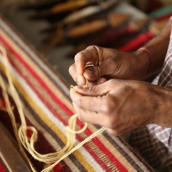 特写:一名女士正在手工编织地毯。