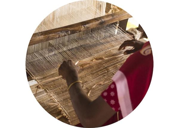 特写:一名女士正在用织布机编织地毯。