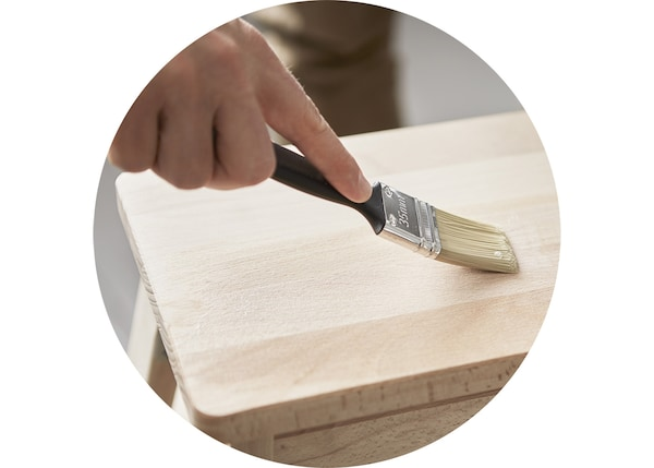 特写:一只手拿着画笔在凳子上涂画。