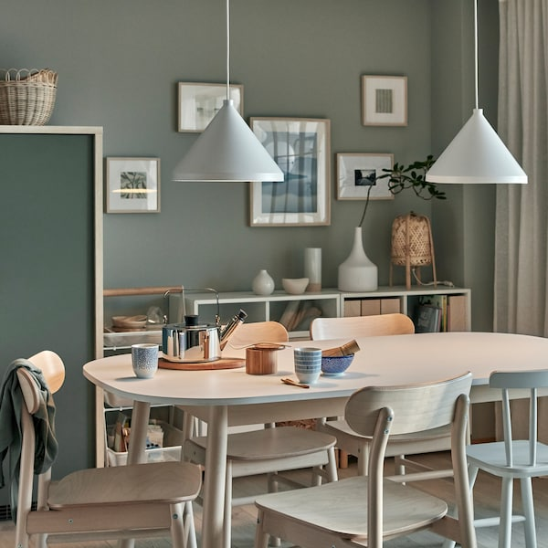 Tea for two is served on a dining table. Two lit NÄVLINGE pendant lamps are above, and they give a cosy, dimmed lighting.