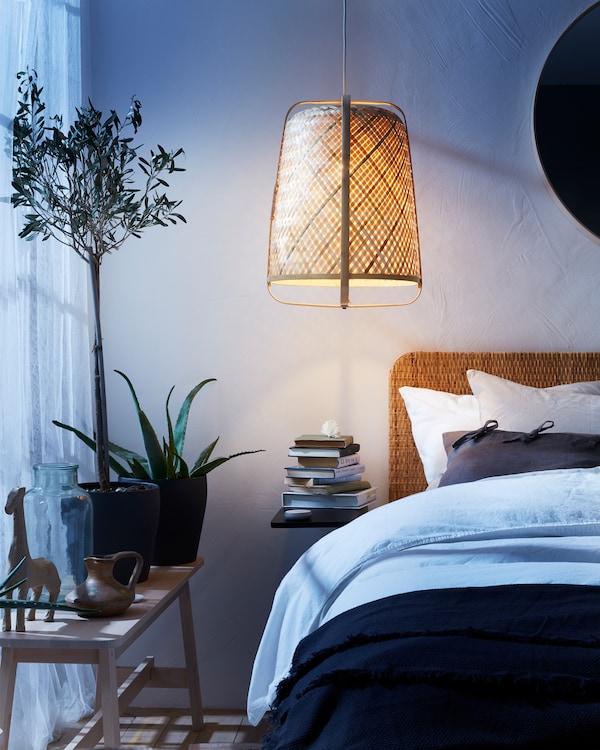 藤条吊灯、长椅、带藤条床头板的床、白色窗帘和花盆中的不同植物。