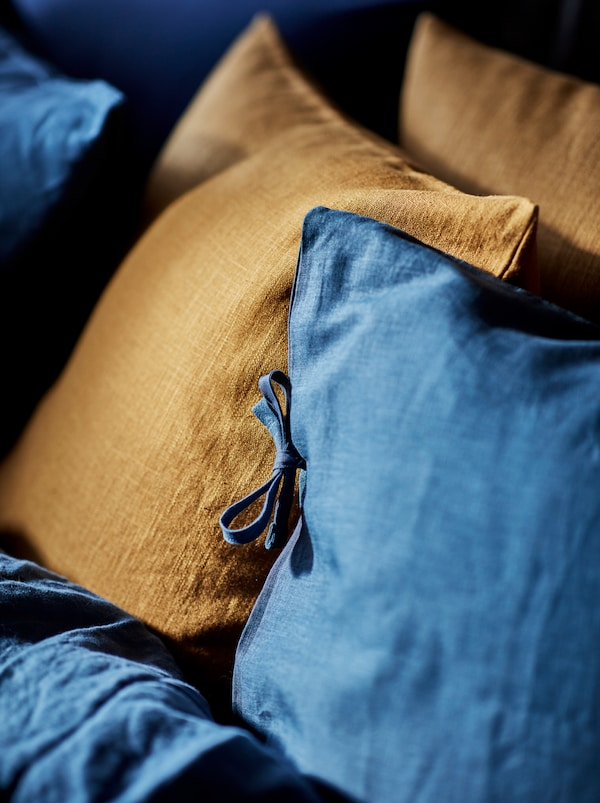 The cover-meets-pillow part of a bed neatly made with blue PUDERVIVA bed linen, a pair of dark-turmeric cushions mixed in.