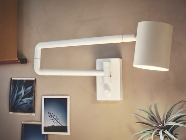 The design of NYMÅNE wall lamp makes it easy to direct. When not in use, it folds flat against the wall.