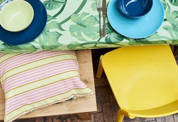 The edge of a table covered with green leaf-print fabric, a yellow dining chair and oak bench with stripy yellow cushion.
