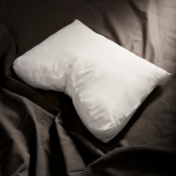 The fluffy IKEA SKOGSLÖK ergonomic pillow shown against dark grey bedlinen.