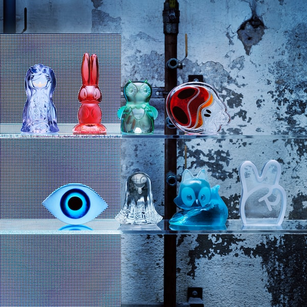 The IKEA Art Event 2018 Limited collection of toy art glass figurines arranged on two glass shelves.
