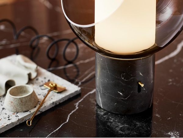 The IKEA EVEDAL table lamp has a sleek globe shape made of glass, with a discreet brass dimming knob. It also has a marble foot and brass details that give your room a modern touch.