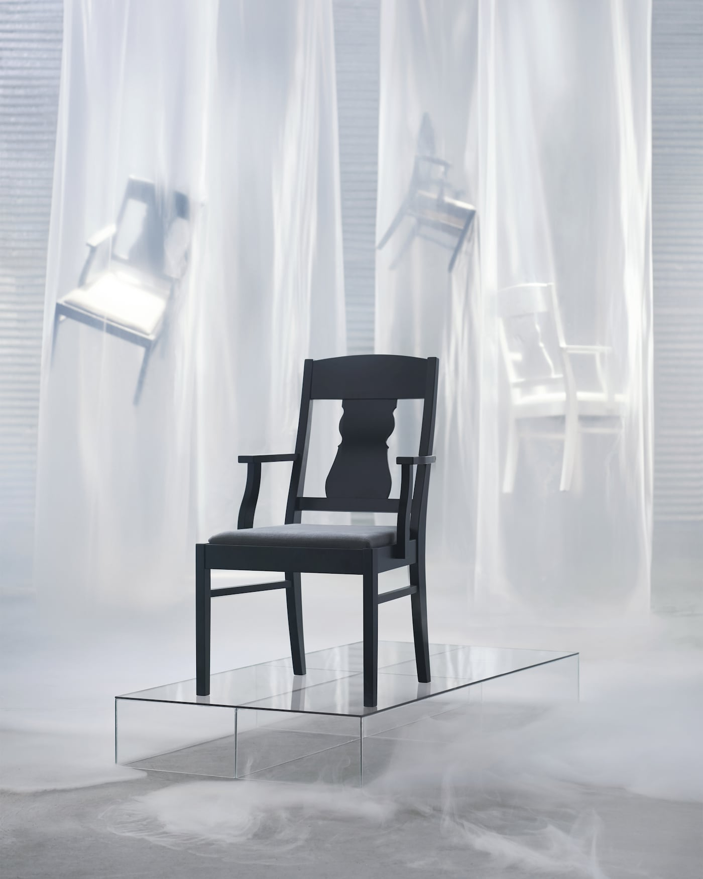 The IKEA INGATORP chair with armrests is available in a black version with a grey cover or a white frame with a beige cover. The chair combines traditional design with features like ornamental details in the back rest with modern upholstered comfort.
