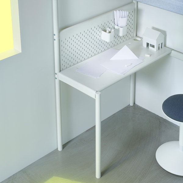 The optional desk underneath VITVAL loft bed, together with a pegboard and desk accessories.