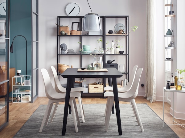 The secret to a stylish dining room? Design icons like award-winning IKEA ODGER recycled plastic white chairs and a bold black LISABO table.