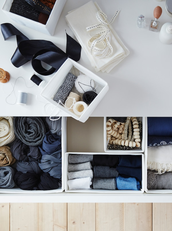 The top of a chest of drawers covered with sewing accessories. An open drawer reveals garments neatly placed in SKUBB boxes.