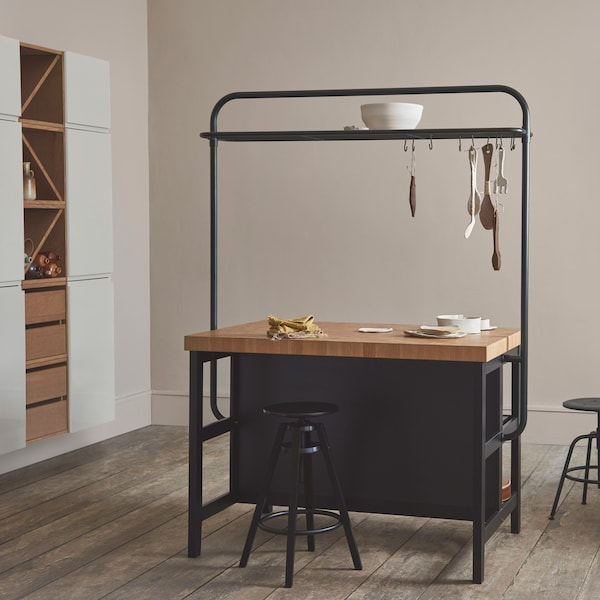 The VADHOLMA kitchen island has a unique butcher block look. It also has a traditional design in brown stained ash and an optional rack for extra storage and hanging utensils.