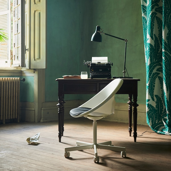 The white LOBERGET/BLYSKÄR swivel chair with a rounded design placed by an old desk near an open window in a green room.