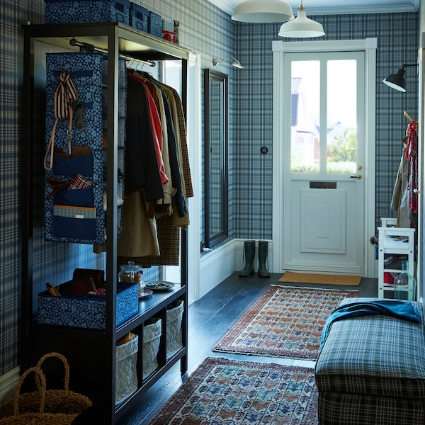 This hallway is all about green toned plaids and cool blue hues. It is organised with the help of IKEA STORSTABBE blue white floral storage boxes.