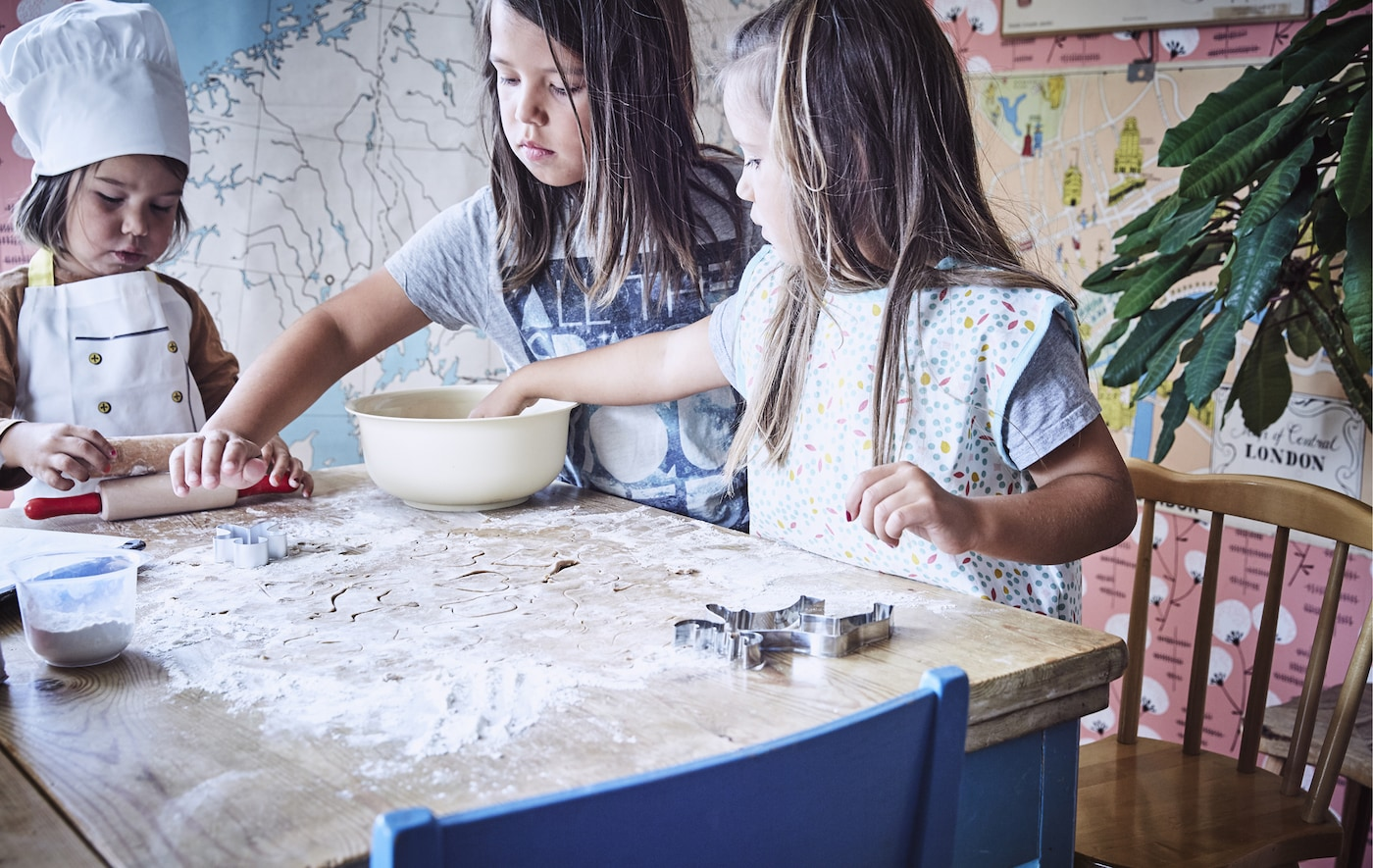 Three children standing around a table with flour, dough and baking utensils.