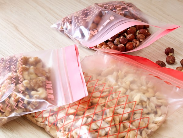 Three ISTAD plastic bags containing different kinds of nuts on a wooden worktop.