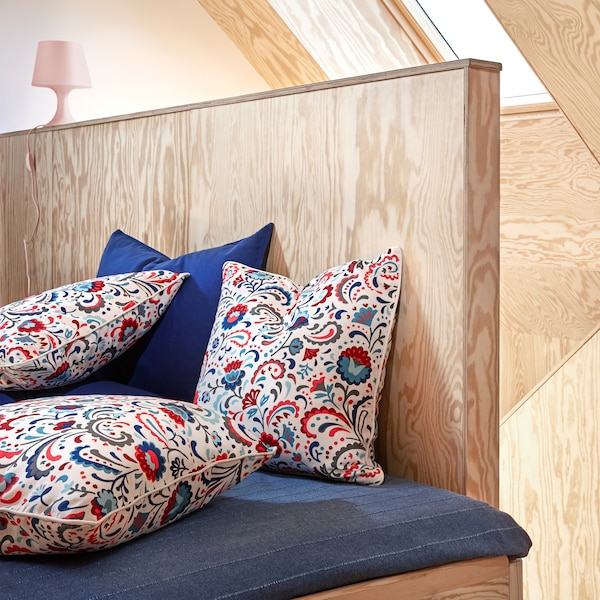 Three KRATTEN cushion covers featuring a floral, Scandinavian traditional pattern in many colours on a white background.
