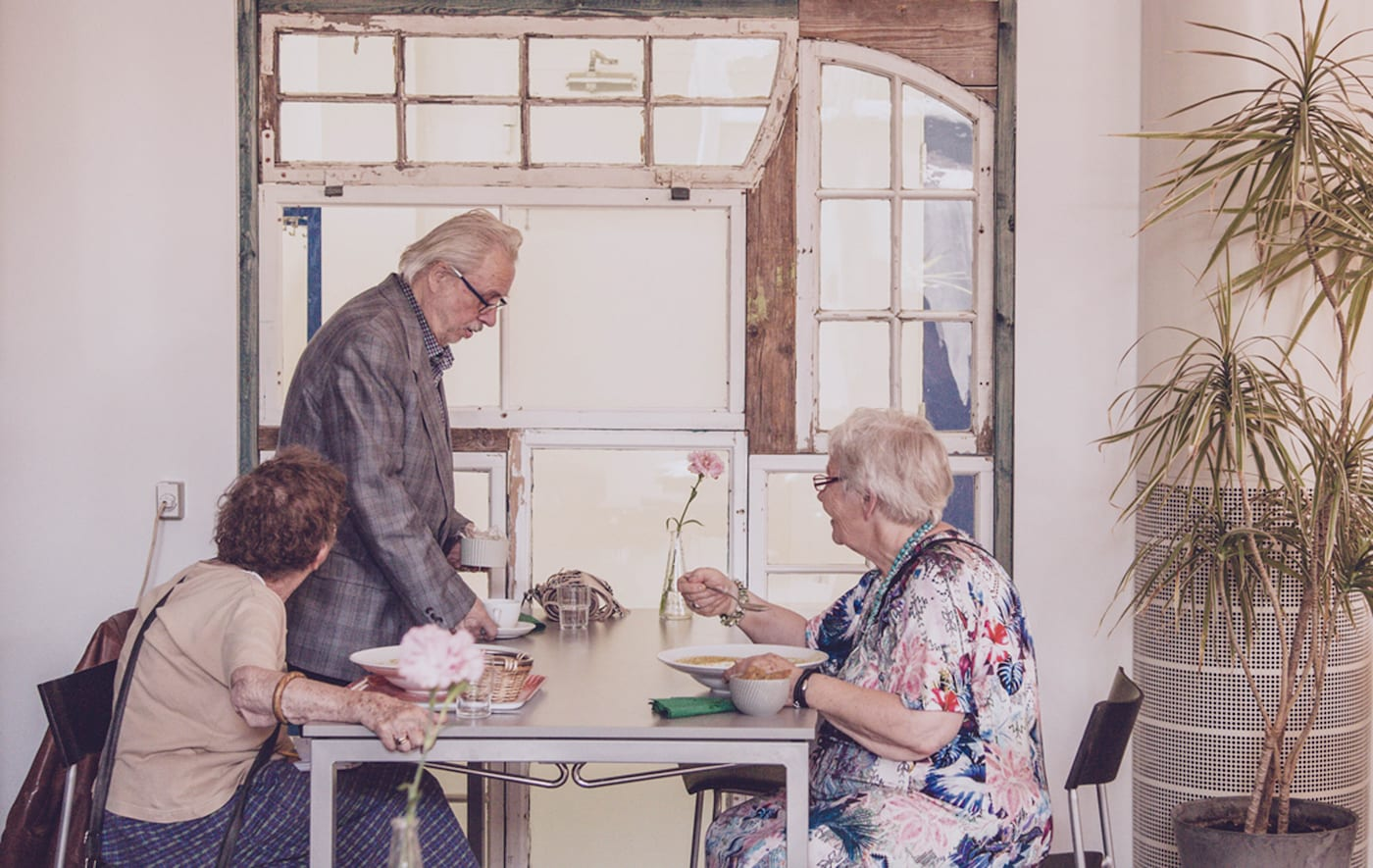 Three older people sit at a table eating a meal together.