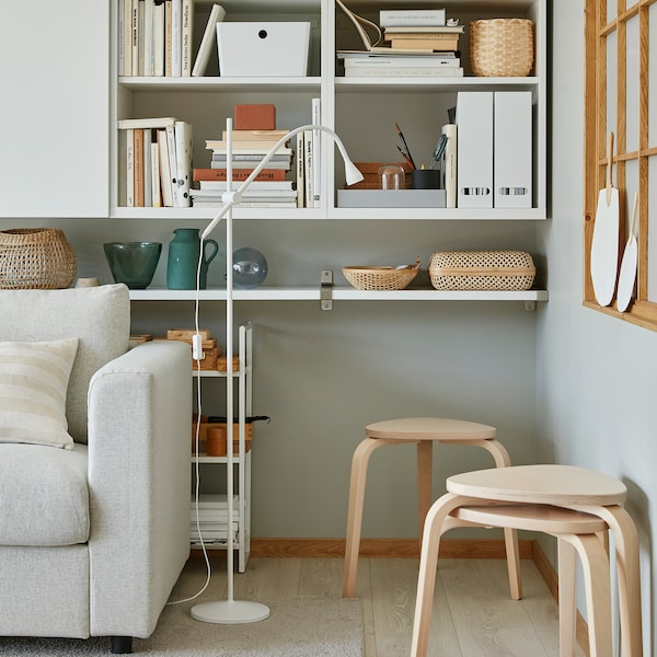 Three stackable KYRRE stools in birch are standing in a living room corner and offer extra seating when needed.