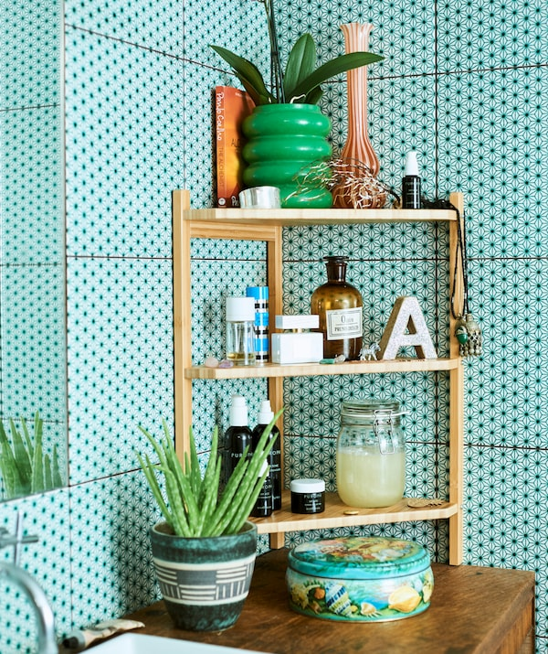 Three-tiered bamboo corner shelf unit with jars, candles and plants, placed on a wood cabinet against green bathroom tiles.
