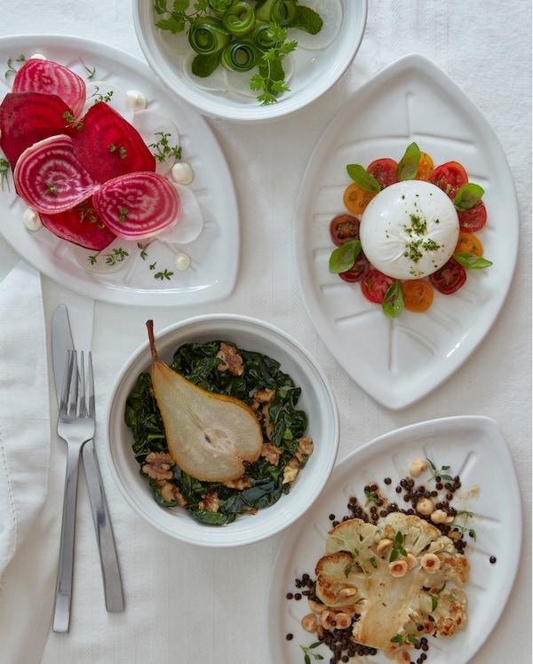 Three white leaf-shaped VINTERFEST plates and two round bowls with savouries on a white tablecloth.