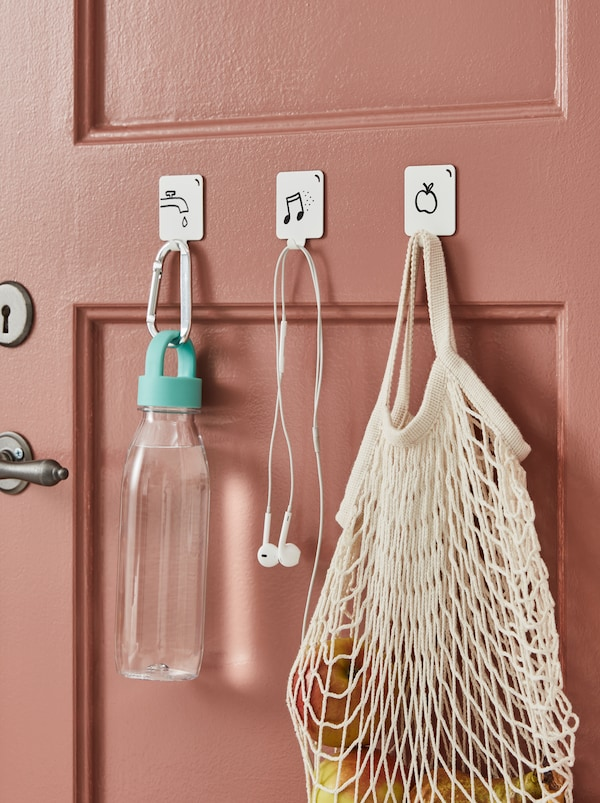 Three white PLUTT self-adhesive hooks attached to a door and decorated with hanging advice made with a black marker.