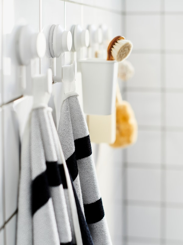 Tiled bathroom wall with a row of TISKEN suction-cup hooks, holding towels, a scrubber, and similar bathroom accessories.