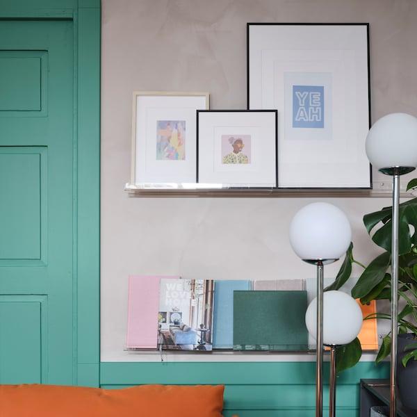 透明壁式图片架上展示着裱框艺术作品和图片、书和淡彩色笔记本。