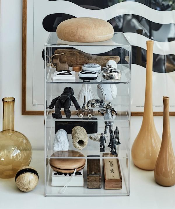 透明抽屉柜里摆放着旧玩具,旁边立着棕色玻璃花瓶。