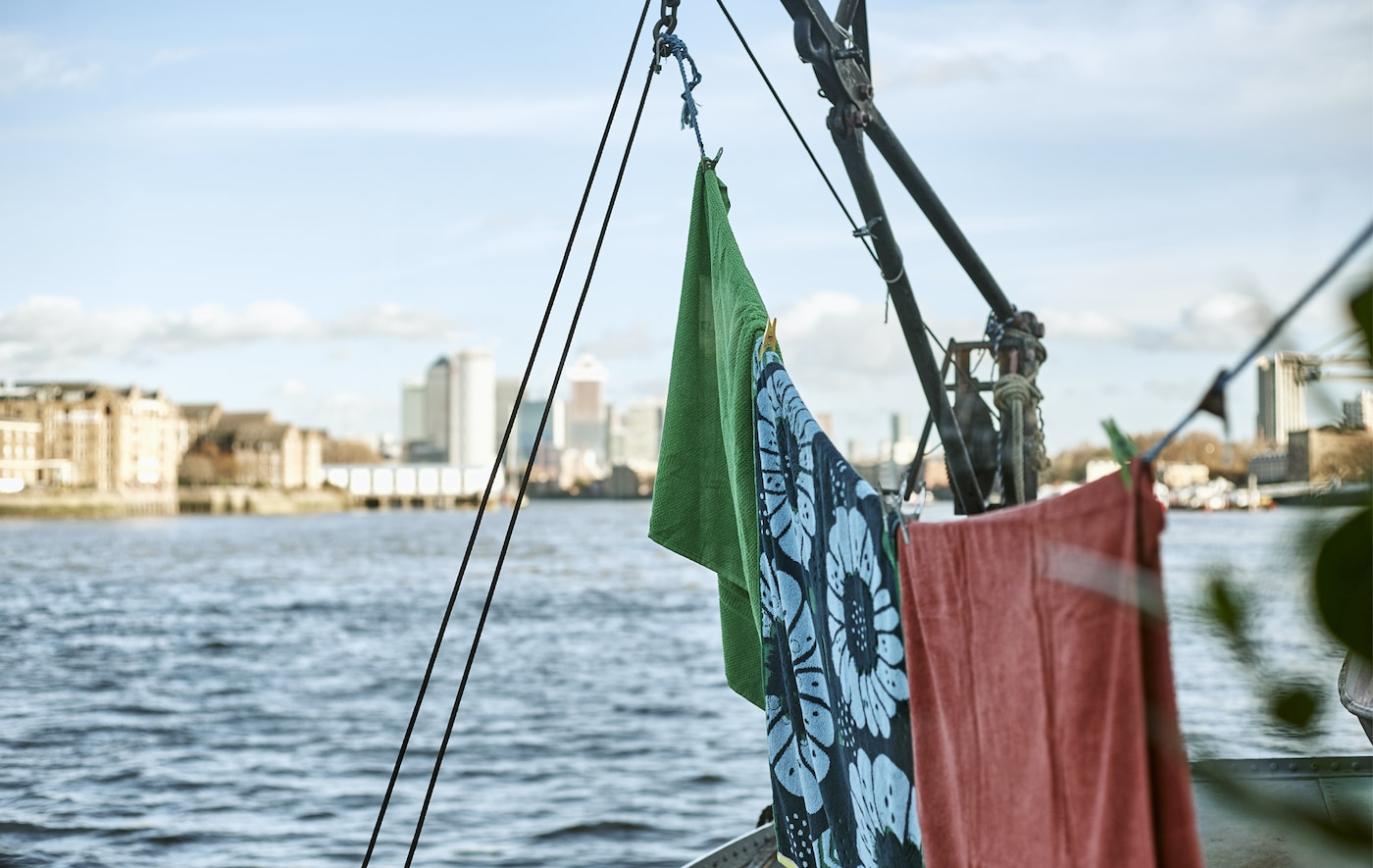 Towels hanging on a line on a boat on the river.