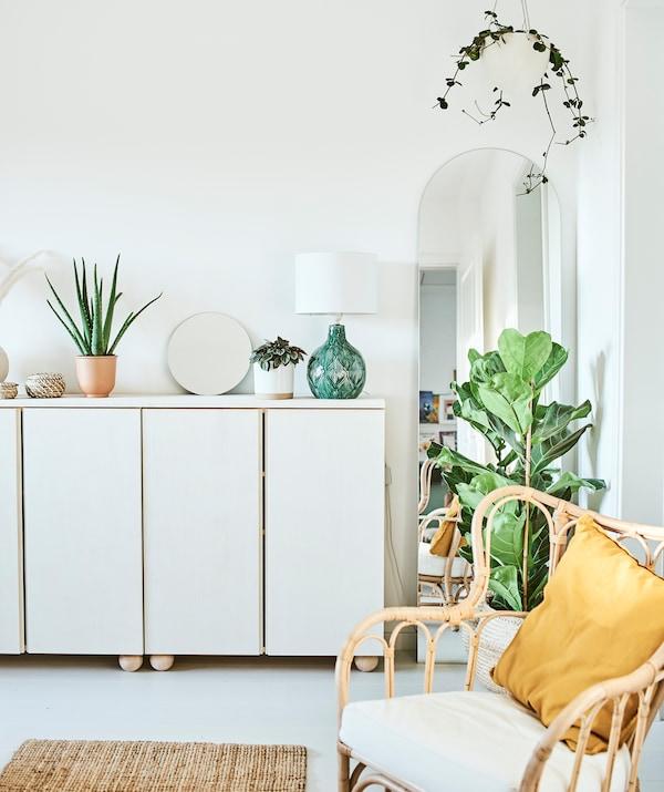 涂成白色的橱柜上放着植物、镜子和绿色灯具,拱形的镜子边缘装饰着垂吊植物。