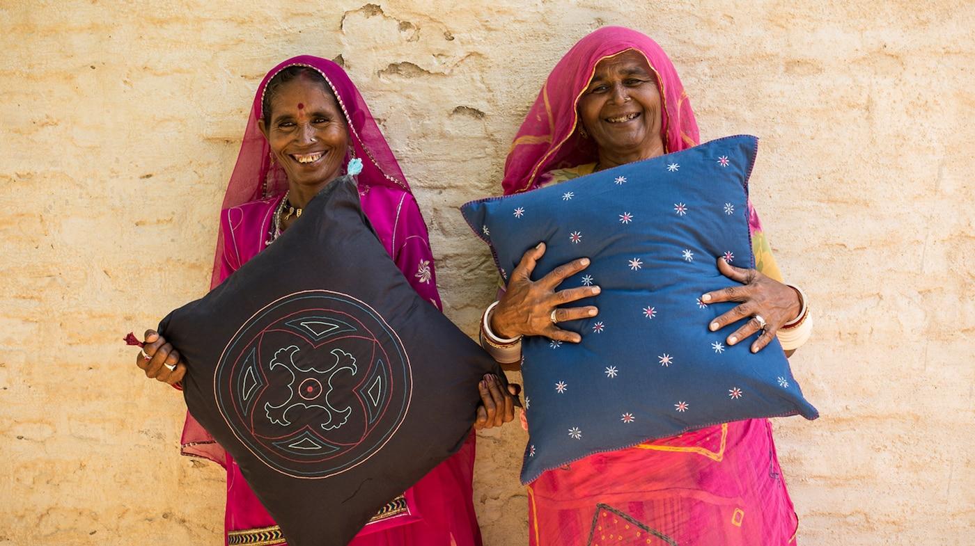 图片显示两家社会企业手举纯手工制作的枕头。他们利用自己的业务来应对社会及环境方面的挑战,例如减少贫困和赋予女性权利。