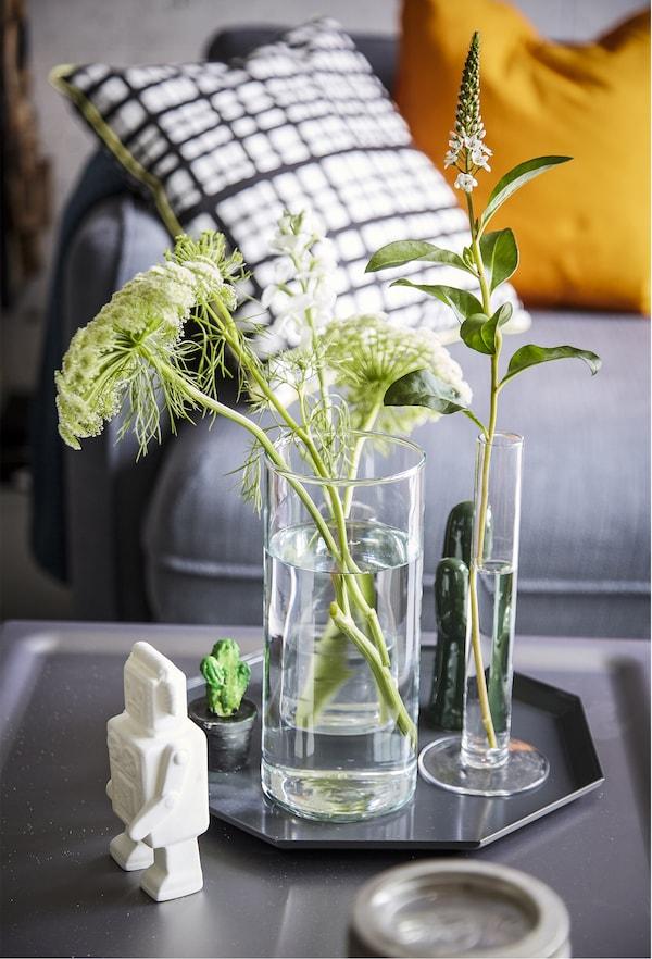 托盘上的花瓶里放着植物枝条。