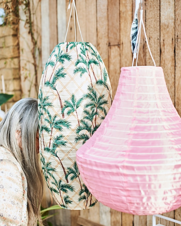 Two big hanging outdoor lanterns, one in pink, the other with palm tree print, partially hiding a woman with long grey hair.