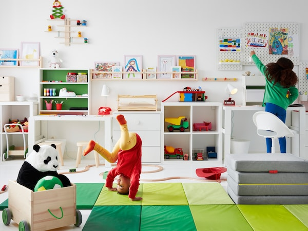 Two children, one in acrobatic motion on a PLUFSIG gym mat, play in a room with toys, storage and drawings up the walls.