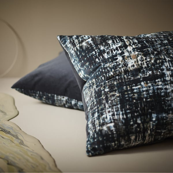 Two cushions shown on the floor, made in cotton velvet with dark colours blended together like an oil painting and with a backside in solid grey.