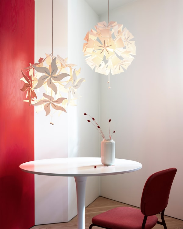 Two different RAMSELE pendant lamps in a flower or geometric shape that can unfold when the strings are pulled.