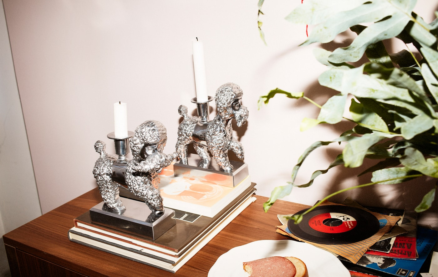 Two dog-shaped candlesticks, books and records on a sideboard.
