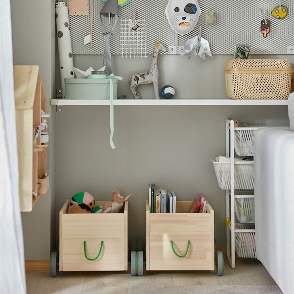 Two FLISAT toy storage units in solid pine with grey wheels and green handles store children's books and more.